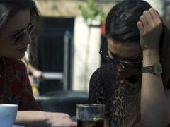 Women consoling her friend in street cafe, steadycam shot - stock footage