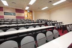 Empty hall for presentation with grey armchairs - stock photo