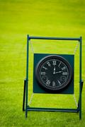 outdoor clock on golf course with green spring valley on the background - stock photo