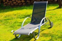 Relax. empty deck chair on grass in garden. Stock Photos
