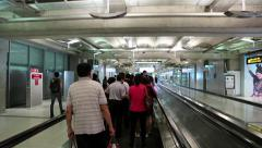 People on travelator inside international airport in Bangkok, Thailand Stock Footage