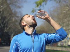 Jogger drinking water in park, slow motion shot at 240fps, steadycam shot Stock Footage