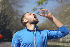 Jogger drinking water in park, slow motion shot at 60fps, steadycam shot Stock Footage