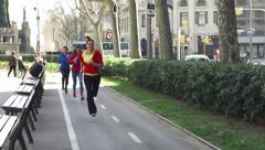 Women jogging on bikelane, slow motion shot at 240fps, steadycam shot Stock Footage