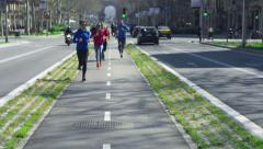 People jogging on the street, slow motion shot at 240fps, steadycam shot Stock Footage