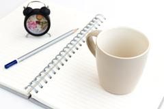 alarm clock and notebook isolated on white - stock illustration