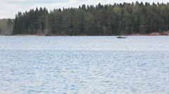 Stock Video Footage of Man boating on rowboat across lake, distance view