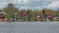 Village on lake shore with wooden buildings, Russia Stock Footage