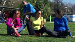 Women sitting on grass and talking, slow motion shot at 60fps Stock Footage