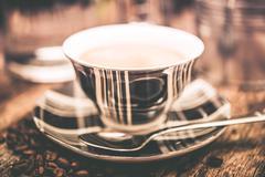 tartan design inprinted coffee cup with spoon closeup. - stock photo