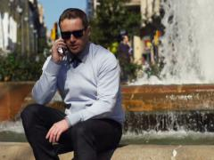 Businessman talking on the phonesitting by the fountain, slow motion shot 240fps Stock Footage