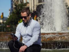 businessman sitting by the fountain and listening to music on his ipod - stock footage