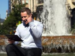 Businessman looking at good results on tablet and sitting by the fountain Stock Footage
