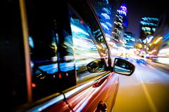 driving through city lights. car side and mirror view. night drive concept - stock photo