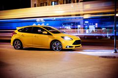 Stop motion car concept. speeding motion blurred traffic and yellow sports ca Stock Photos