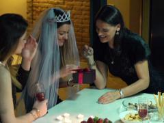 Young woman opening a gift at the bachelorette party, slow motion shot at 240fps Stock Footage