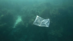 Plastic bag floating underwater over coral reef - stock footage