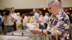 old woman puts electoral billeting in the ballot box. - stock footage