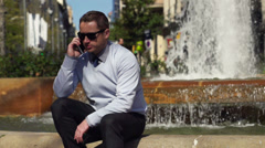 Businessman talking on the phone  sitting by the fountain, slow motion  240fps Stock Footage