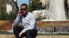 Businessman talking on the phone and sitting by the fountain, slow motion 60fps Stock Footage