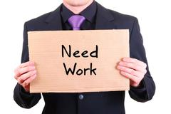"""Unemployed businessman with cardboard sign """"Need Work"""" Stock Photos"""