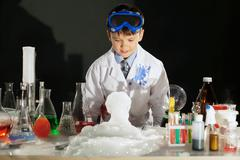Adorable smart boy doing experiment in studio - stock photo