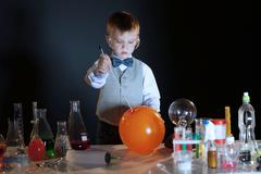 Image of concentrated pupil pierces balloon in lab Stock Photos