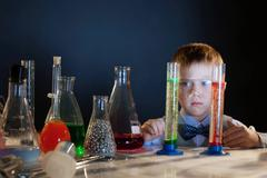 Handsome little boy posing with test-tubes - stock photo