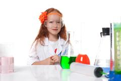 Smiling red-haired schoolgirl posing in lab - stock photo