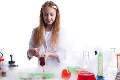 Curious schoolgirl mixes reagents in studio Stock Photos
