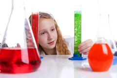 Lovely schoolgirl looking at flasks with chemicals - stock photo