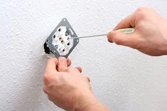 Electrician installing wall socket Stock Photos