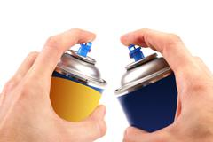 Two graffiti color spray cans in hands Stock Photos