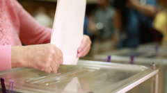 Women's hands are placed electoral billeting in the ballot box. - stock footage