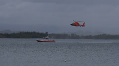 Us coast guard rescue helicopter flying low hovers behind coast guard boat 11 Stock Footage