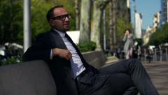 Businessman sitting on a bench in the city, slow motion shot at 60fps Stock Footage