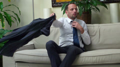 Businessman taking clothes off after work and sitting on the sofa Stock Footage