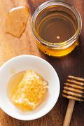 honeycomb dipper and honey in jar on wooden background - stock photo