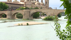 Tilt up on old stone bridge over river and catholic basilica Pilar Stock Footage