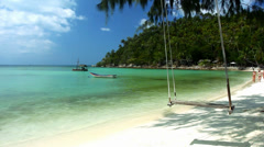 Swaying swing on the shore of a tropical island and a womans running along the Stock Footage