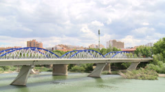 Time lapse on clouds and iron bridge ) over river Ebro , traffic  Stock Footage