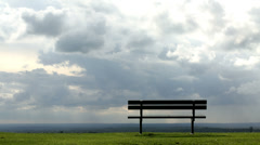Time lapse of clouds rolling past a single bench - stock footage