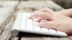 HD Close-up of a little girl hand typing on a laptop keyboard on old wood table - stock footage