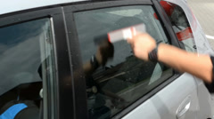 Man washing car window with window cleaner Stock Footage