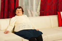 Senior woman relaxing on sofa Stock Photos