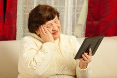 Sad elderly woman looking at photo frame Stock Photos