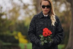 Young woman at graveyard with fresh roses Stock Photos