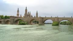 Basilica of El Pilar with stone bridge and large river, tilt Stock Footage
