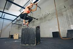 female athlete is performing box jumps at gym - stock photo
