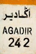 Sign road with distance to agadir - stock photo